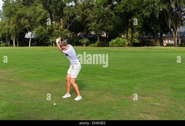 Young woman taking a shot on the fairway of a golf course at the Grenelefe Resort, Haines City, Central Florida, - Stock Image