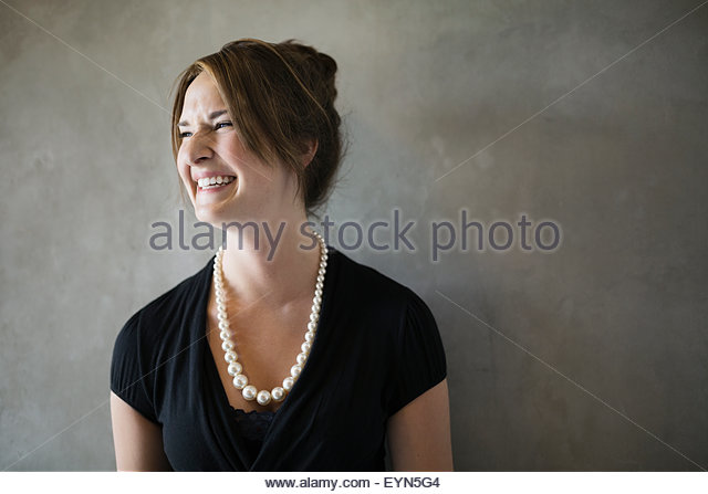 Enthusiastic businesswoman laughing and looking away gray background - Stock Image