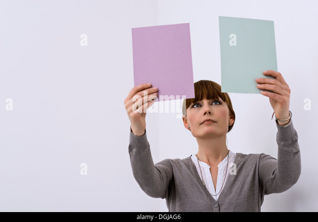 Female designer comparing color samples - Stock Image