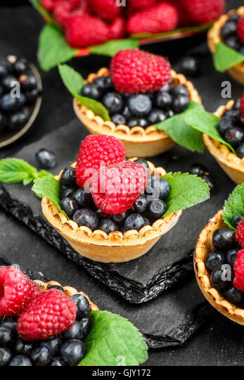 Tartlets with blueberries, raspberries and mint leafs on a black slate background - Stock Image