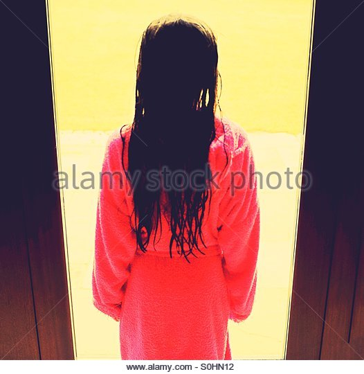 Ghostly child at the window with bathrobe and wet hair - Stock Image