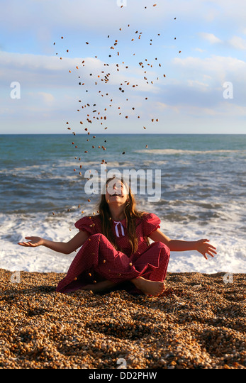 a girl sitting at the beach, throwing pebbles - Stock Image