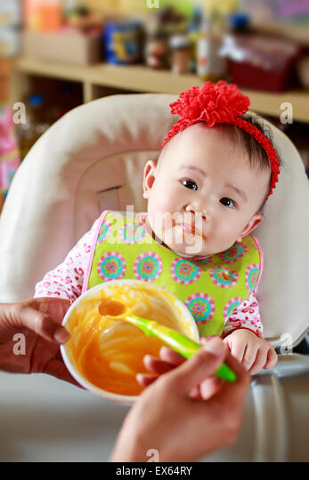 Baby Eating Solid Food - Stock Image