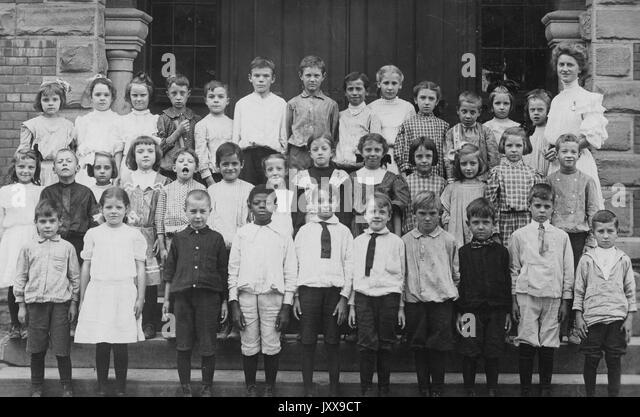 Landscape shot full length portrait of a group of schoolchildren standing in rows, on female teacher on the left, - Stock Image