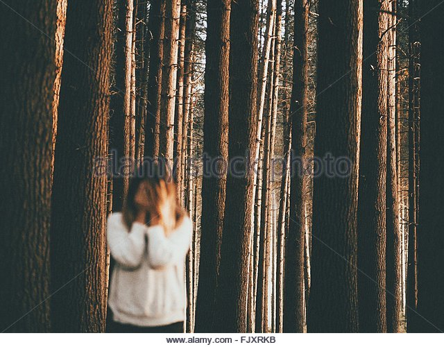 Sad Woman Standing Against Trees In Forest - Stock Image