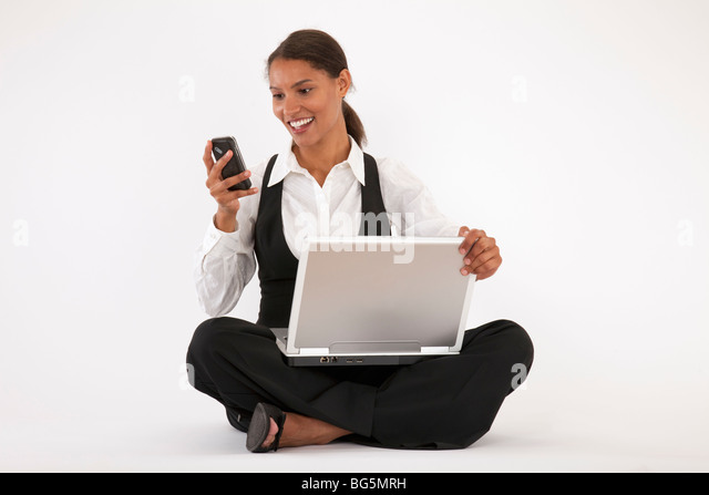 Young woman sitting on floor using laptop and cell phone. Horizontally format. - Stock Image
