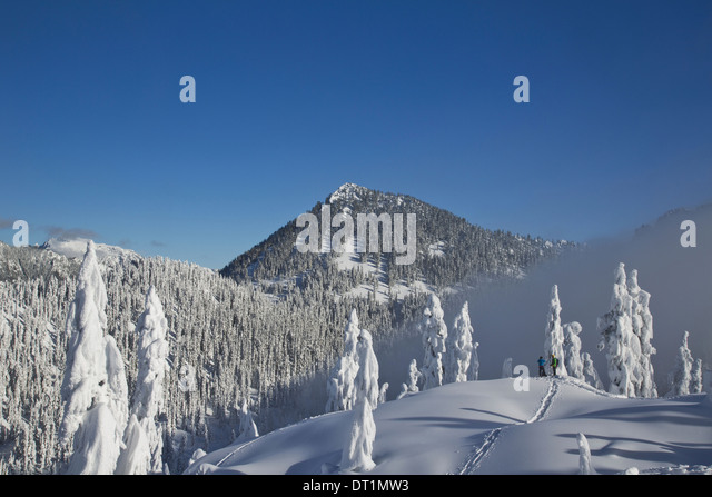 Two hikers enjoy a blue bird day in the middle of winter in the snow covered Cascade Mountains - Stock Image