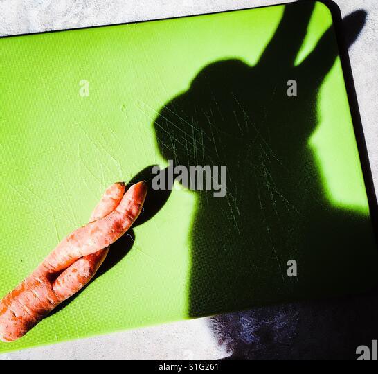 Rabbit shadow eating an unusual carrot - Stock-Bilder