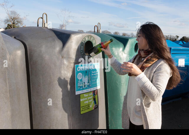 A young woman recycling glass wine bottles, Suffolk UK - Stock Image