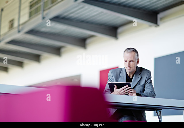 Businessman using digital tablet in lobby - Stock Image