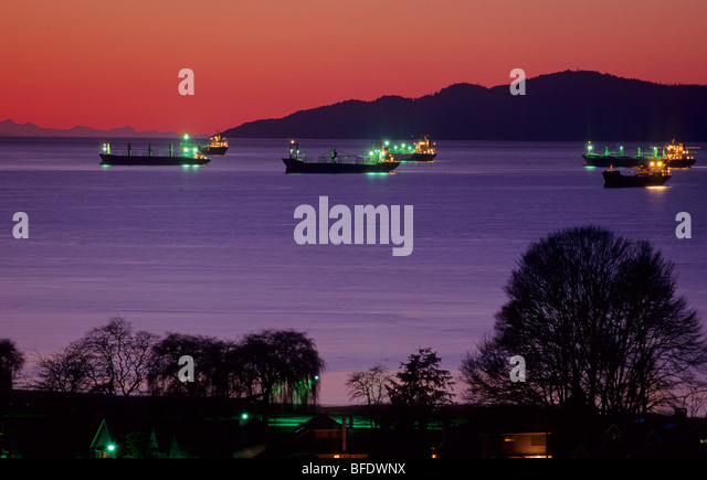 Freighters off the coast of Engish Bay at night, Vancouver, British Columbia, Canada - Stock Image