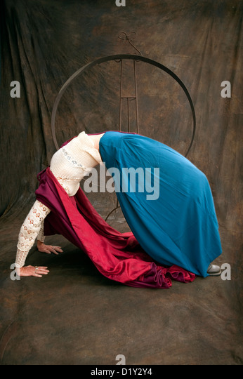 Wise Woman Red Riding Hood. Mature woman in a deep acrobatic backbend in a studio environment. - Stock Image