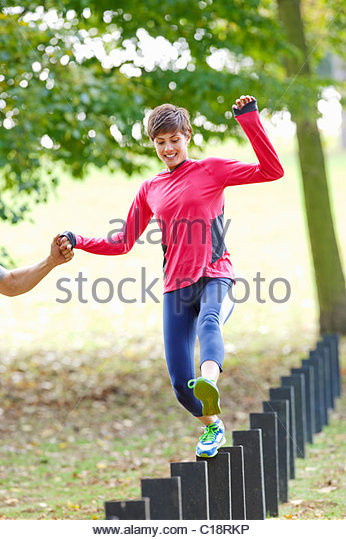 Woman jumping post during workout - Stock Image