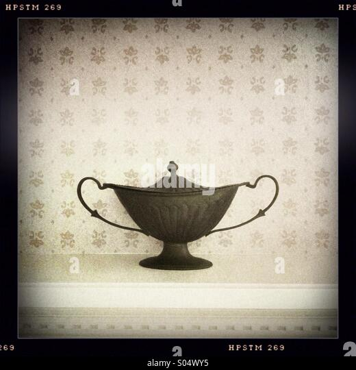 A small metal urn on a decorative shelf - Stock Image