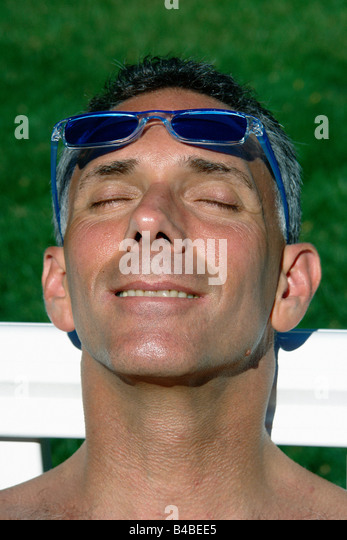 Head and Shoulders Portrait of a Man Soaking in the Sun He is Smiling and has his Sunglasses on his Forehead - Stock Image