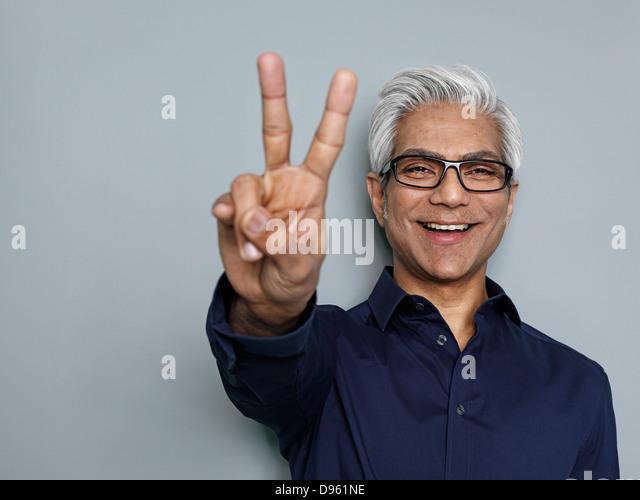 Businessman gesturing peace sign, smiling - Stock-Bilder