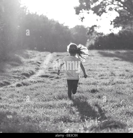 Rear view of girl running in rural landscape - Stock Image