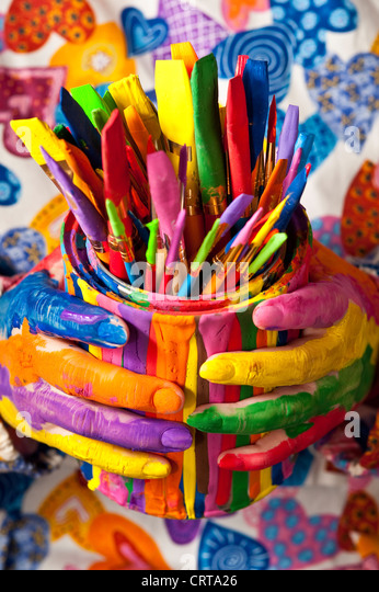 Close-up of woman holding multicolored paint can with painted fingers - Stock Image