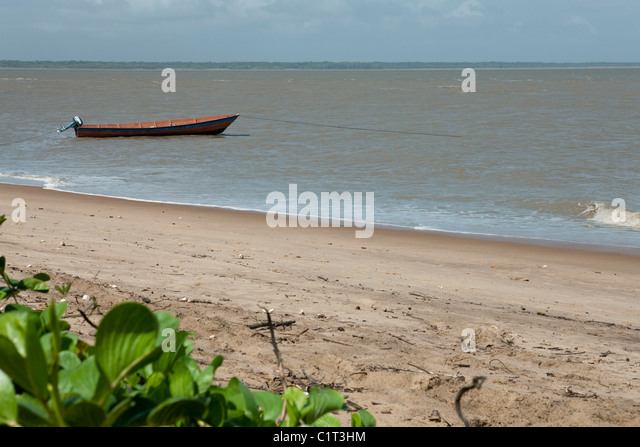 Boat moored along sandy shore - Stock Image
