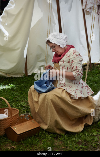 A woman sews at the Claude Moore Colonial Farm market fair, McLean, Virginia, where it is always 1771. - Stock Image