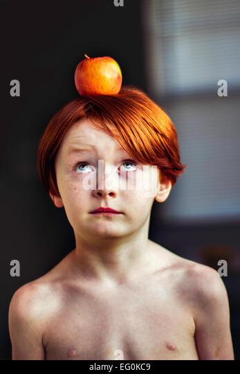 Boy balancing an apple on his head - Stock-Bilder