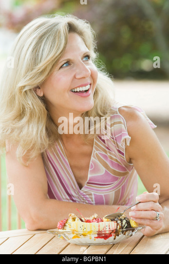Mature woman eating an ice cream - Stock-Bilder