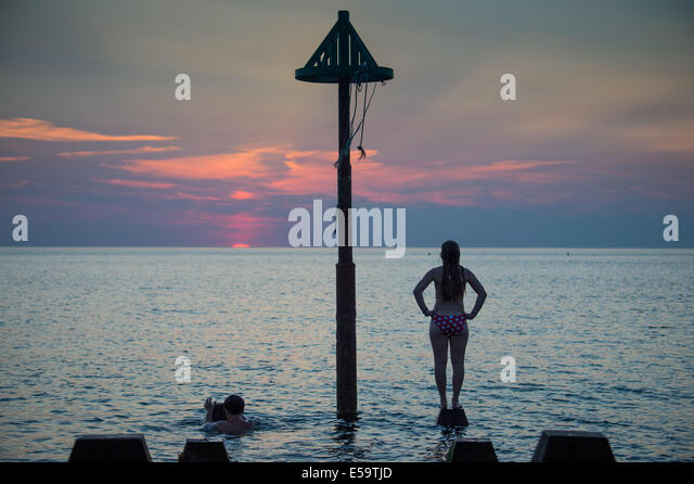Aberystwyth, Wales, UK. 24th July, 2014. A young woman watching the sunset, twilight over Cardigan Bay Aberystwyth - Stock Image
