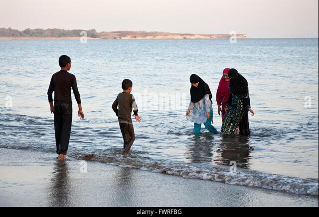 Muslim family relaxing at Nagoya Beach. Diu. Union Territories of Daman and Diu. India - Stock Image