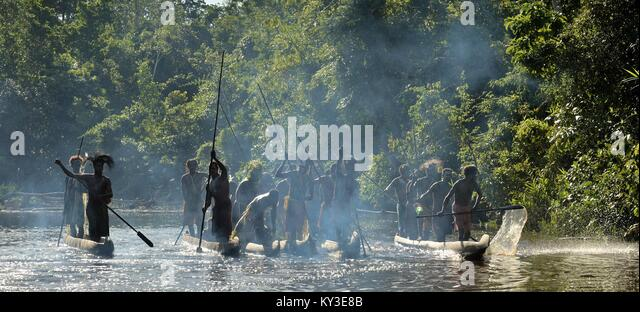 INDONESIA, IRIAN JAYA, ASMAT PROVINCE, JOW VILLAGE - MAY 23: Silhouettes of asmat warriors on the boats. Canoe war - Stock Image