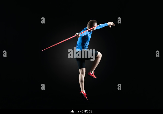 Male athlete leaping with javelin - Stock Image