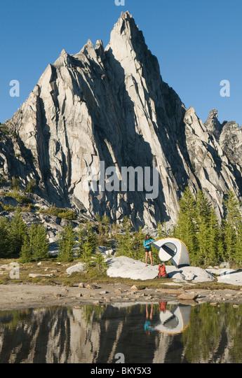 A woman camping on a pristine, alpine lake below a peak, Enchantment Peaks, Alpine Lakes Wilderness, Leavenworth, - Stock Image