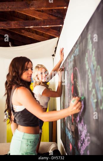 Young women drawing on blackboard - Stock-Bilder