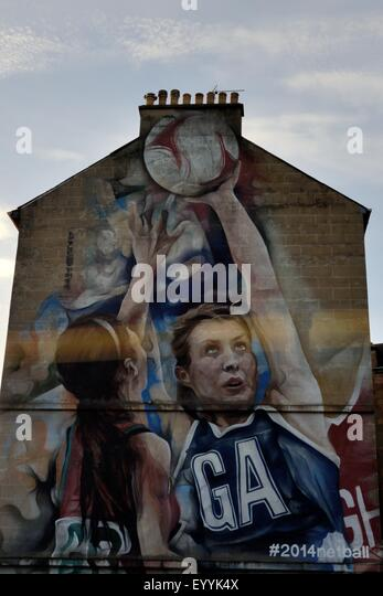 A large mural on the side of a terrace of house in Glasgow depicts netball players to mark the 2014 Commonwealth - Stock Image