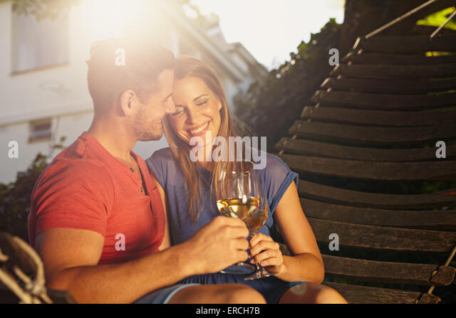 Beautiful young couple toasting wine outdoors. They are sitting on a hammock smiling and drinking wine with bright - Stock-Bilder
