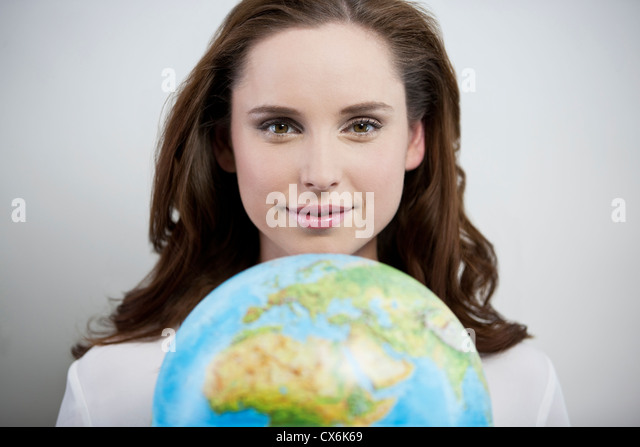 A young woman holding a globe, smiling - Stock Image