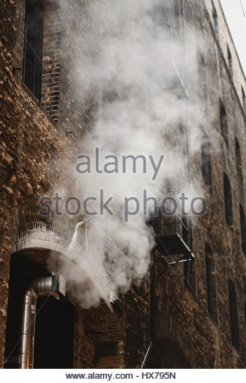 Brick urban building with steam - Stock Image