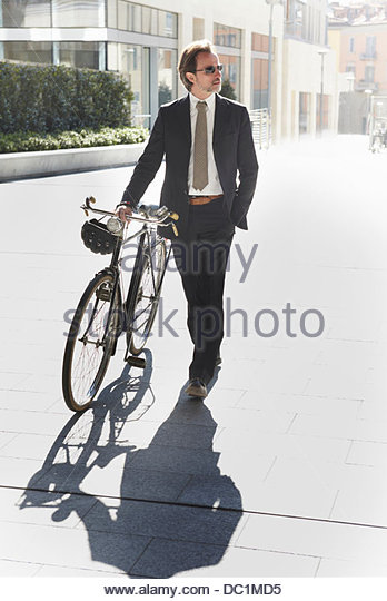 Mid adult businessman walking with bicycle in city - Stock Image
