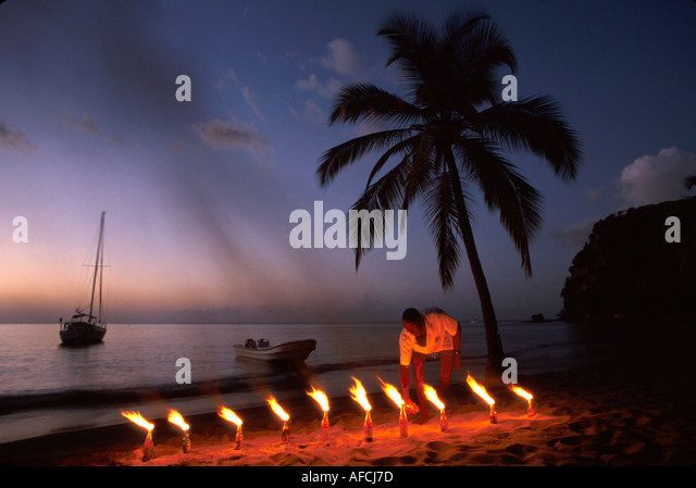 West Indies St. Lucia Anse Chastanet Resort Caribbean Sea Black male lights flambeaus fire flame beach palm tree - Stock Image