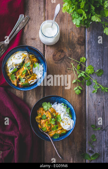 Aubergine curry with coriander and rice in bowls - Stock Image