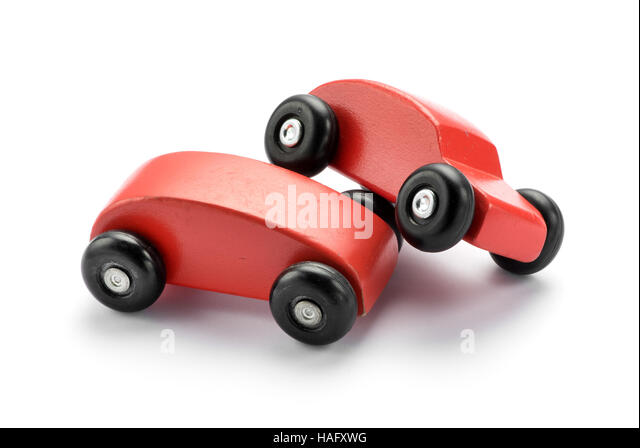 Two stylized toy wooden red cars pile on one another conceptual of a motor vehicle accident or collision, on white - Stock Image