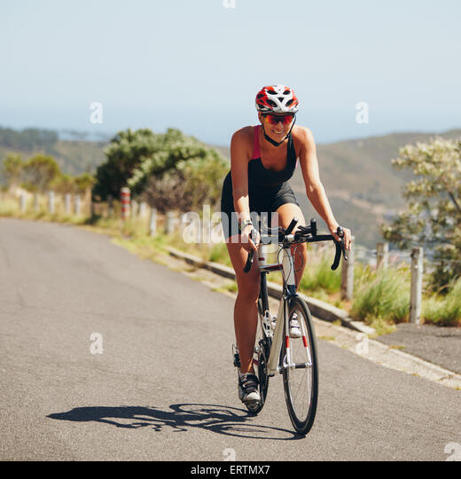 Woman triathlon athlete cyclist down hill on country road. Young woman riding bicycle on open road, practicing for - Stock Image