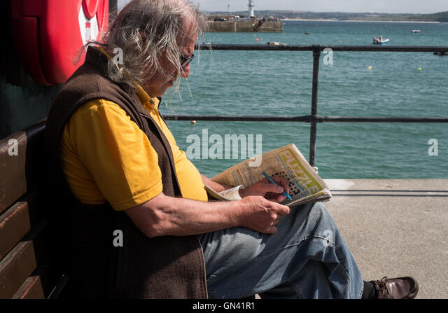Man sat on bench at battling with the wind as he tries to complete the crossword in the newspaper. St Ives, Cornwall - Stock Image