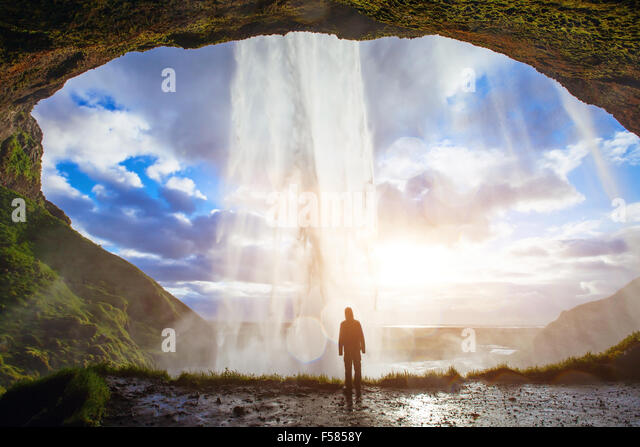 incredible waterfall in Iceland, silhouette of man enjoying amazing view of nature - Stock Image