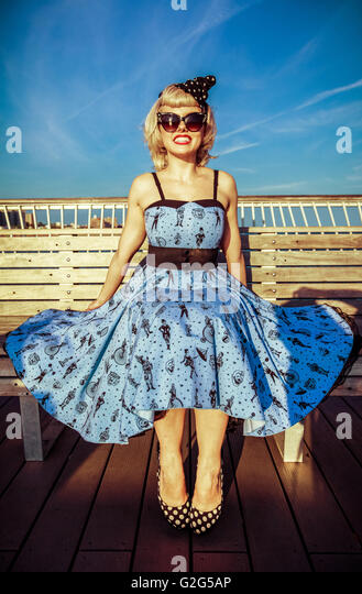 Young Adult Woman in Retro Dress and High Heels Sitting on Boardwalk Bench at Beach - Stock-Bilder