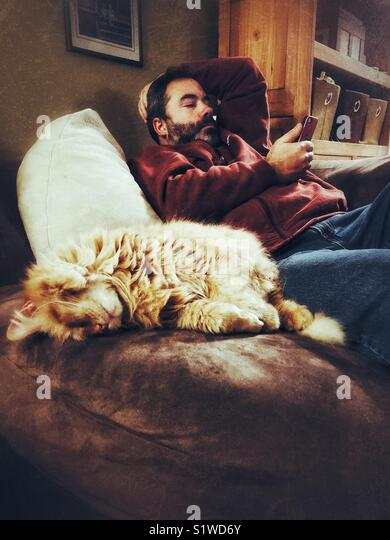 Man with dark beard relaxing on sofa chair using smartphone with large orange cat sleeping in a cute position beside - Stock Image