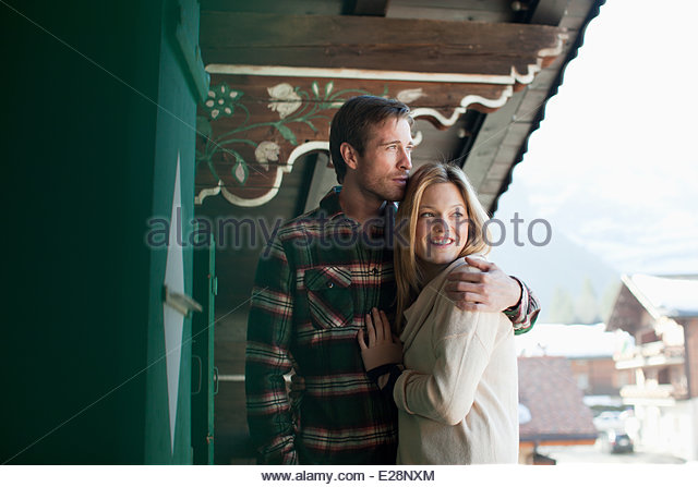 Smiling couple hugging on cabin porch - Stock-Bilder