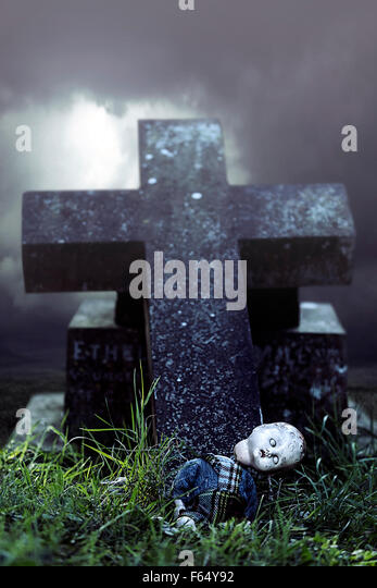 a broken doll on a grave - Stock Image