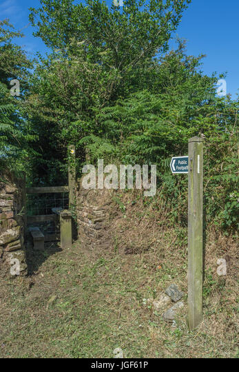 Public footpath sign and country stile in hedgerow cavity. - Stock Image