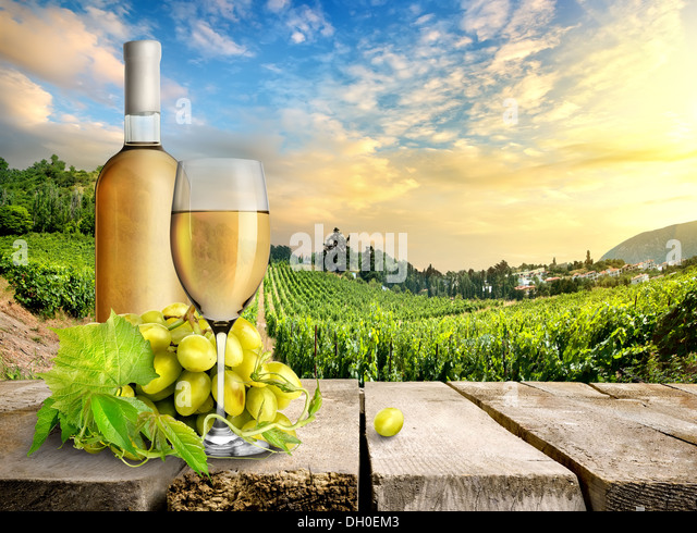 Wine with grape on a background of vineyard - Stock Image