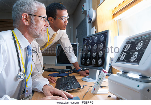 Surgeon and radiologist viewing digital brain scan in hospital - Stock Image